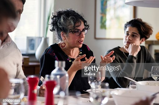 Mature woman gesturing while talking with friends at dining table : Stock Photo