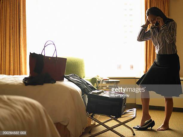 Mature woman getting dressed in hotel room, talking on cell phone