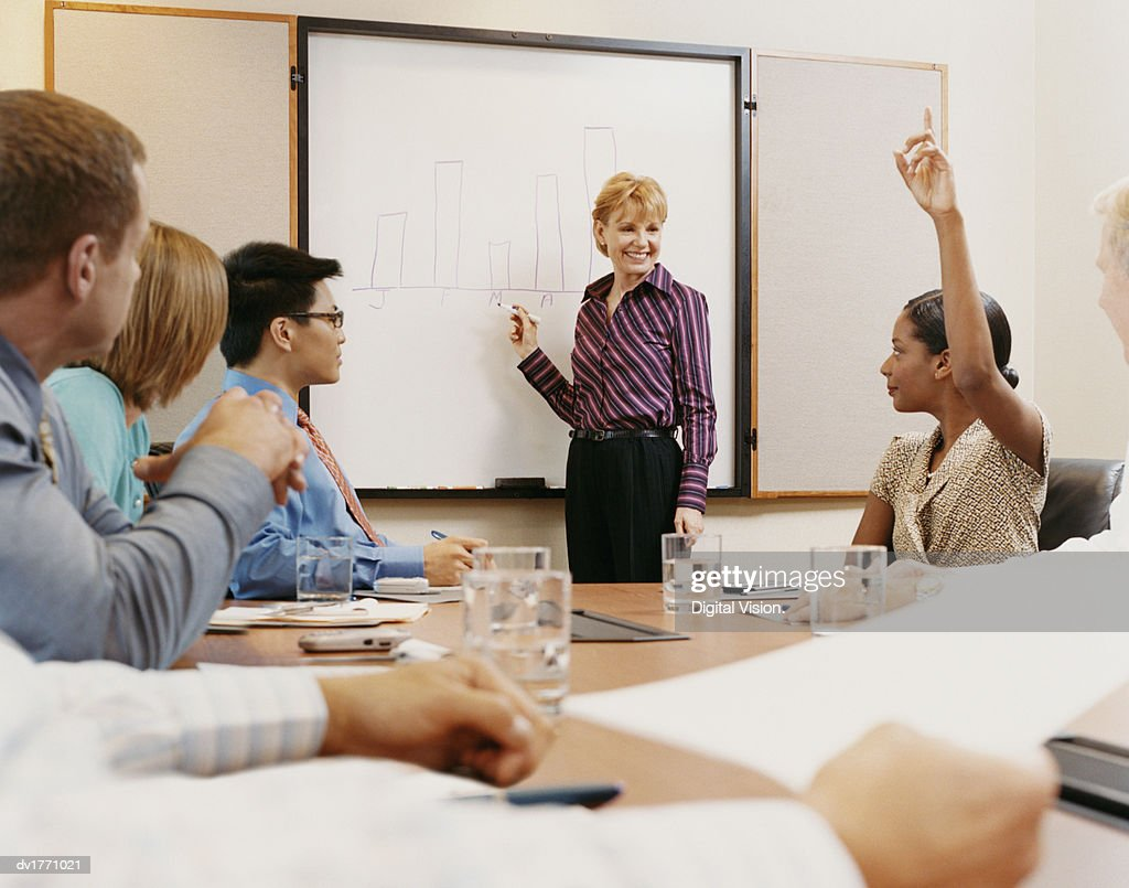 Mature Woman Gives a Business Presentation to a Conference Room of Corporate Executives : Stock Photo