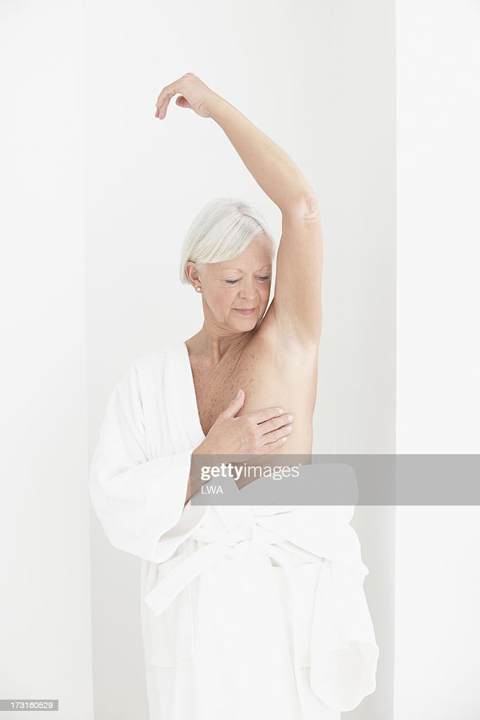 Mature woman giving self breast exam
