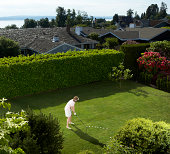Mature woman golfing in backyard