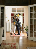 Mature woman greeting man in home