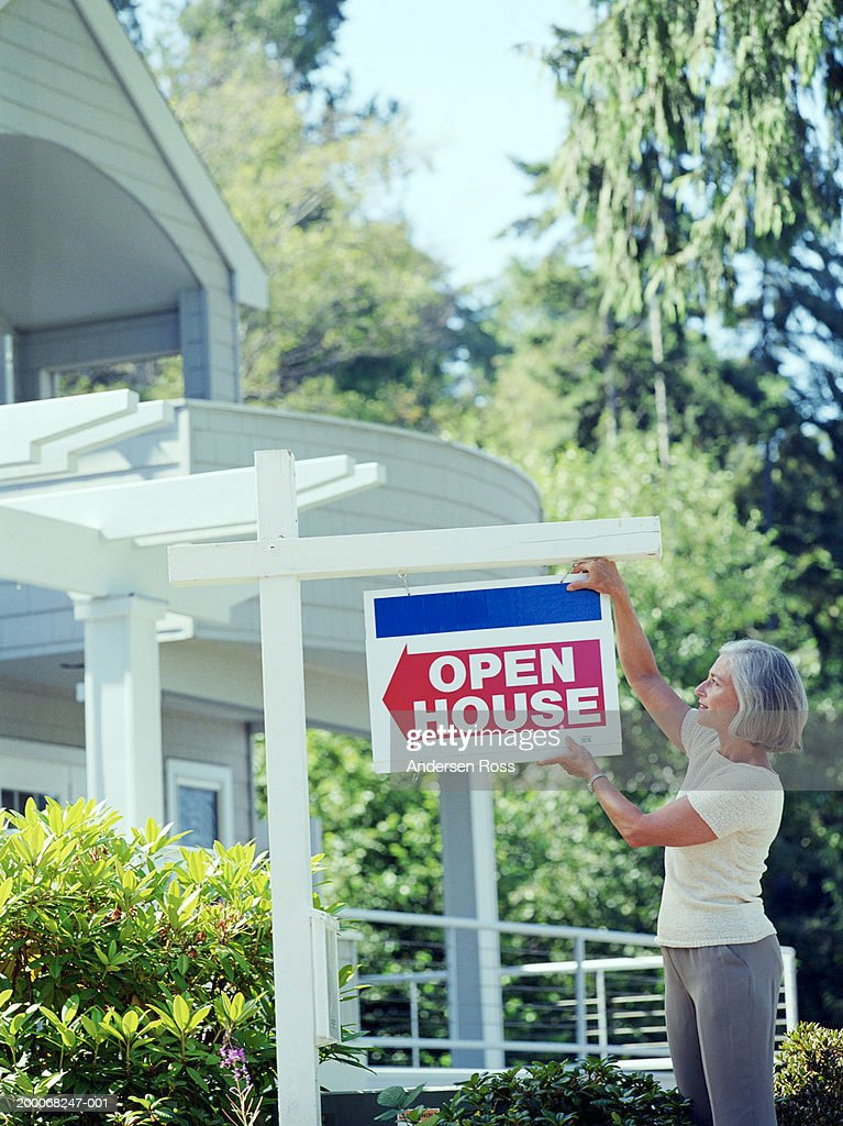 Mature woman hanging Open House sign in front of house : Stock Photo