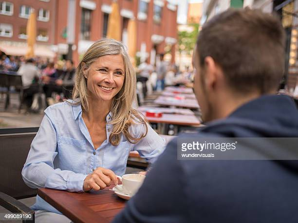 Mature woman having a cup of coffee outdoors with guy