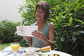 Mature woman having breakfast in garden reading post, smiling