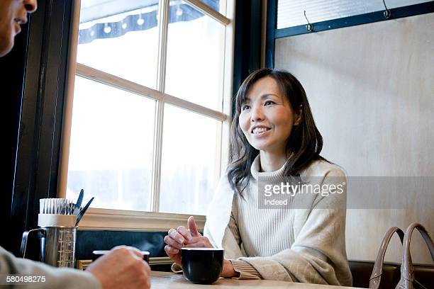 Mature woman having coffee with senior man at cafe