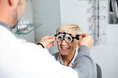 Smiling mature woman having eyesight exam and diopter measurement at the ophthalmology clinic. Healthcare and medicine concept