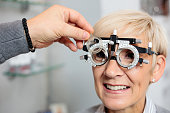 Smiling mature woman having eyesight exam and diopter measurements at the ophthalmology clinic. Close-up photo. Healthcare and medicine concept
