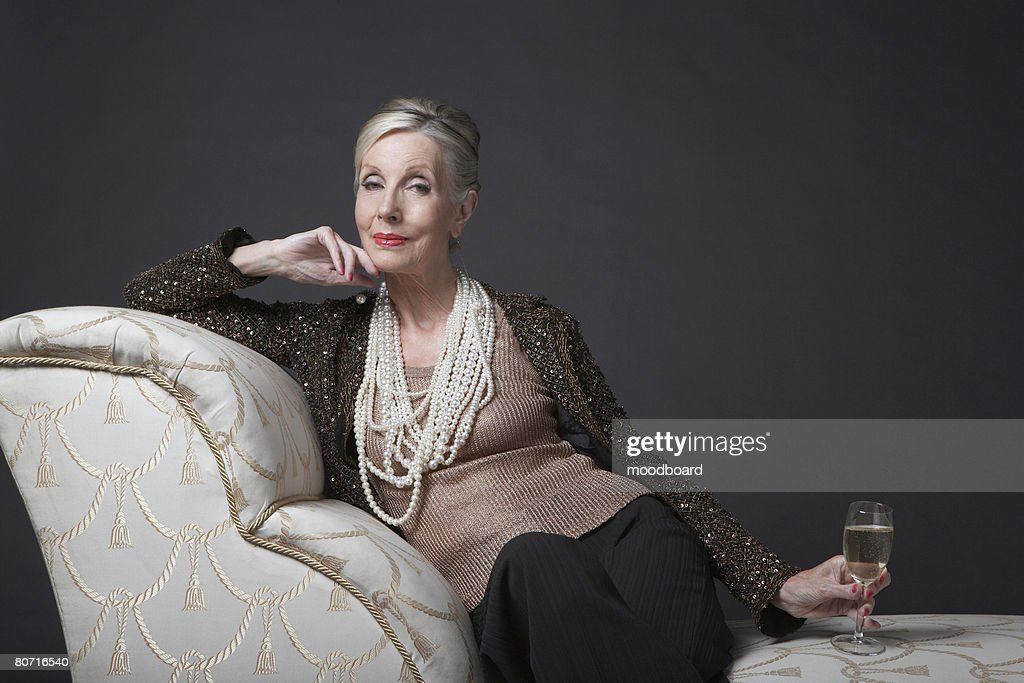 Mature Woman Having Glass of Champagne