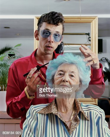 Mature woman having hair styled by male hairdresser