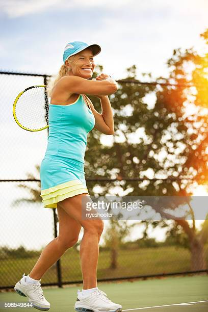 Mature woman hitting forehand winner
