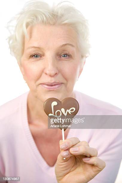 A mature woman holding a chocolate heart with the word Love in her hand