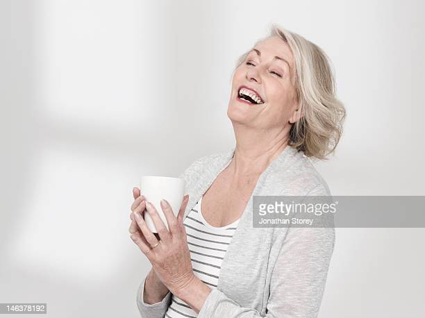 Mature woman holding a mag, open mouth laughing
