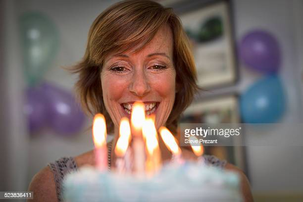 Mature woman holding birthday cake with candles