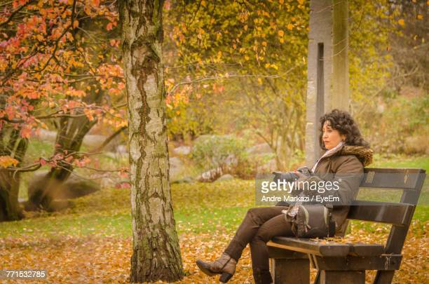 Mature Woman Holding Camera Sitting On Bench In Forest During Autumn