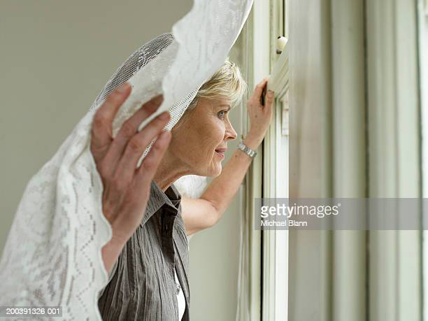 Mature woman holding curtain looking out of window