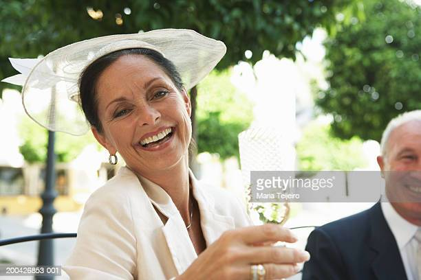 Mature woman holding glass of champagne, smiling, portrait