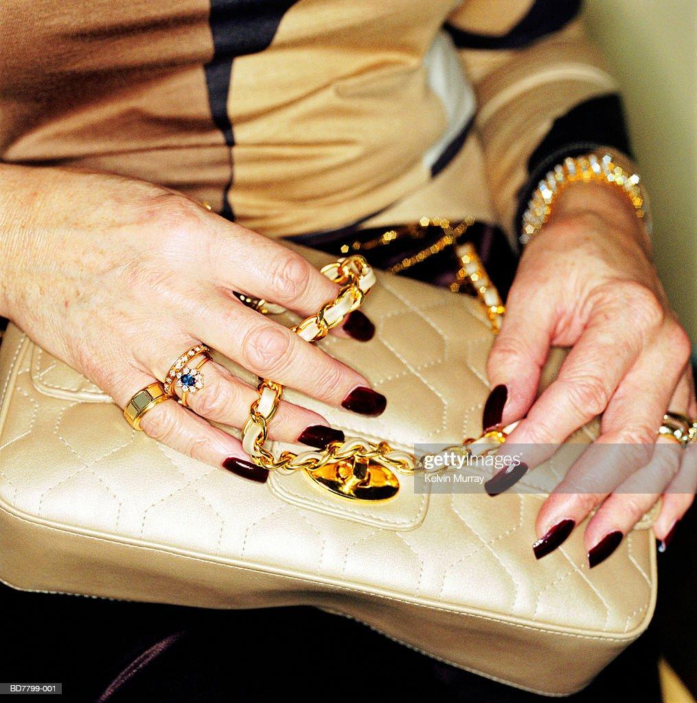 Mature woman holding handbag, close-up