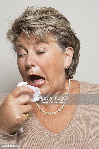 Mature woman holding handkerchief about to sneeze, close-up