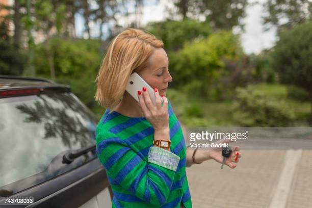 Mature woman holding key while talking through mobile phone by car on road
