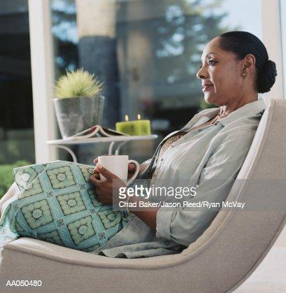 Mature woman holding mug, sitting on porch, side view : Stock Photo