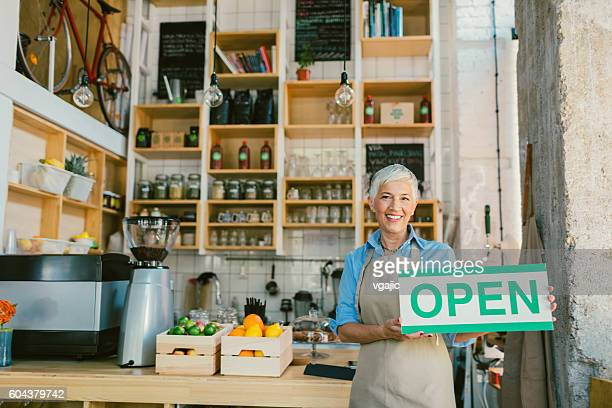 Mature Woman Holding Open Sign In Her Smoothie Cafe
