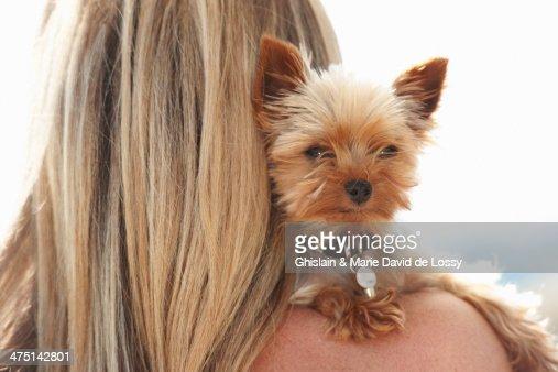Mature woman holding pet dog over shoulder
