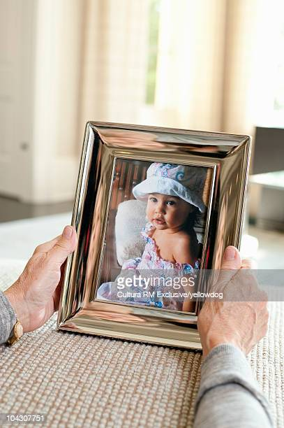 Mature woman holding photo of baby