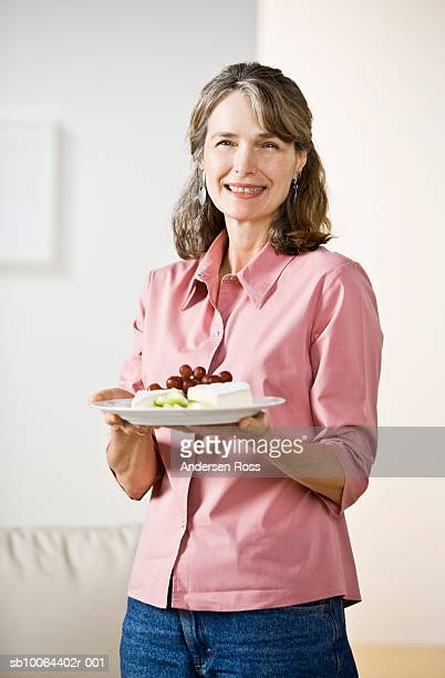 Mature woman holding plate of cheese in home, portrait