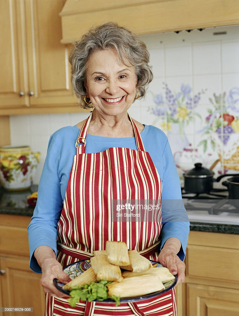 Mature woman holding platter of tamales
