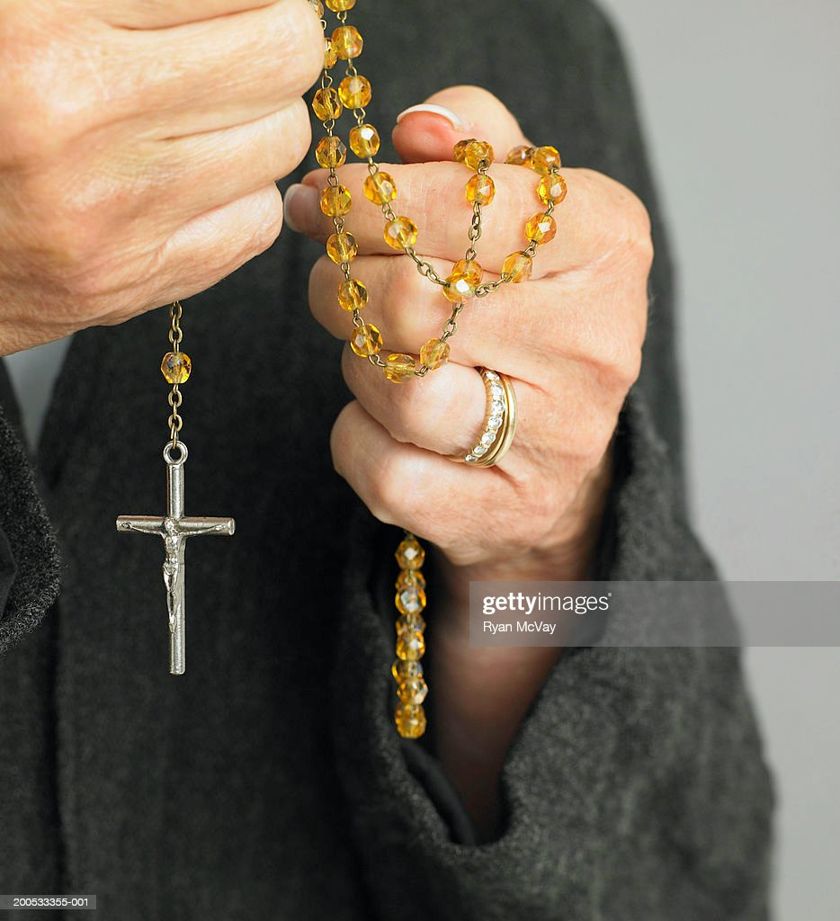 Mature woman holding rosary beads, mid section