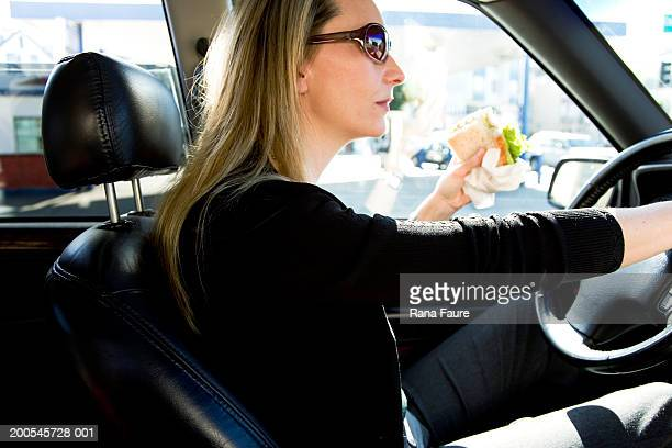 Mature woman holding sandwich and driving car, side view, close-up