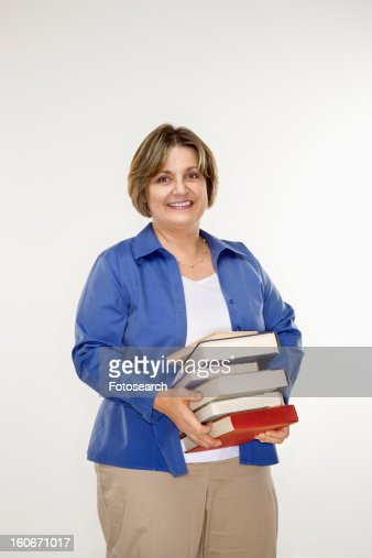Mature woman holding stack of books.
