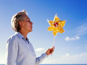 Mature woman holding toy windmill, sea in background (blurred motion)