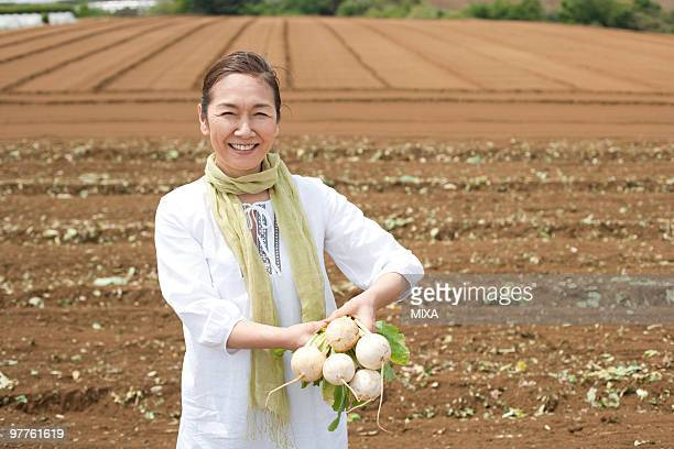 Mature woman holding turnip on field
