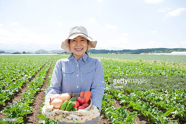 Mature woman holding vegetable on field