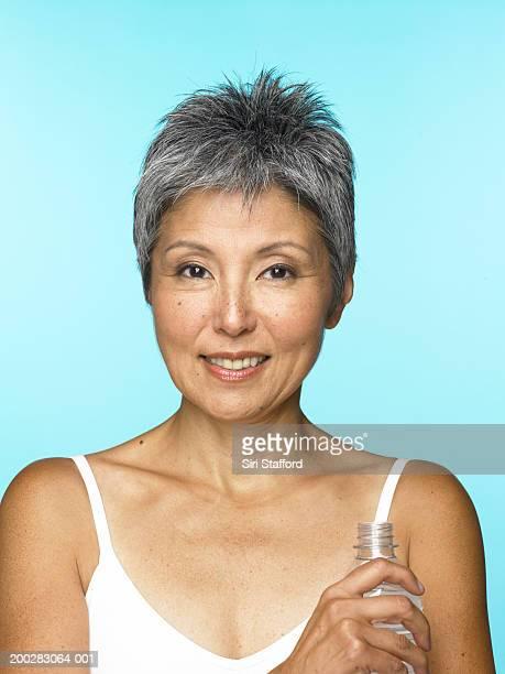 Ältere Frau hält eine Flasche Wasser