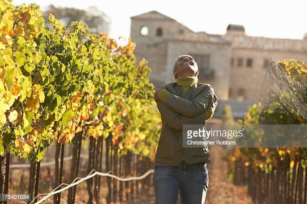 Mature woman hugging self in vineyard, looking up, smiling