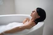 Relaxed lady in her forties relaxing in a modern soaking tub