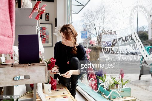 A mature woman in a gift shop by the window, holding a small star.