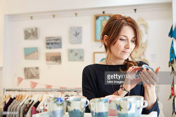 A mature woman in a gift shop holding a small china cup in her hands.