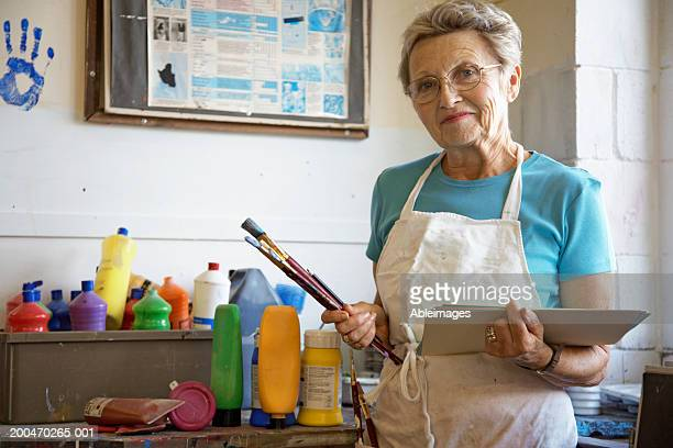 'Mature woman in art classroom, holding brushes and paper, portrait'