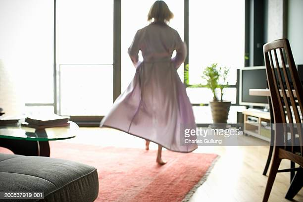 Mature woman in bathrobe walking across living room, rear view