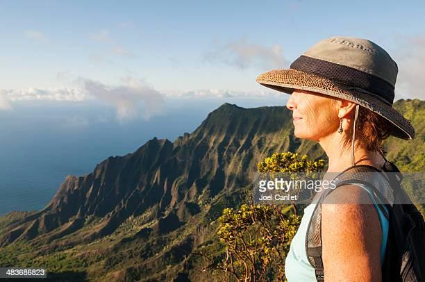 Donna matura nel bellissimo paesaggio in Kalalau Lookout, Kauai