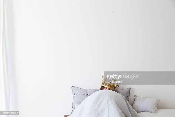 Mature woman in bed underneath quilt wearing golden crown