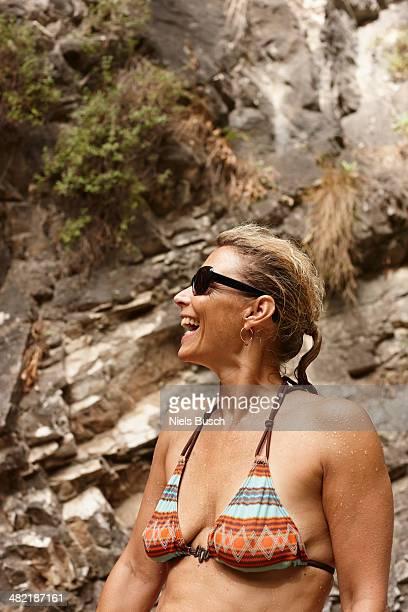 Mature woman in bikini and sunglasses laughing
