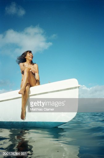 Mature woman in bikini sitting on edge of boat, smiling