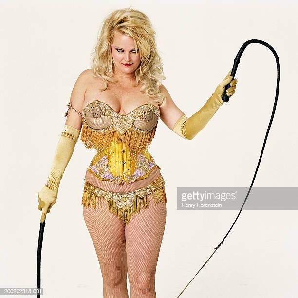 Mature woman in costume, holding whips, portrait