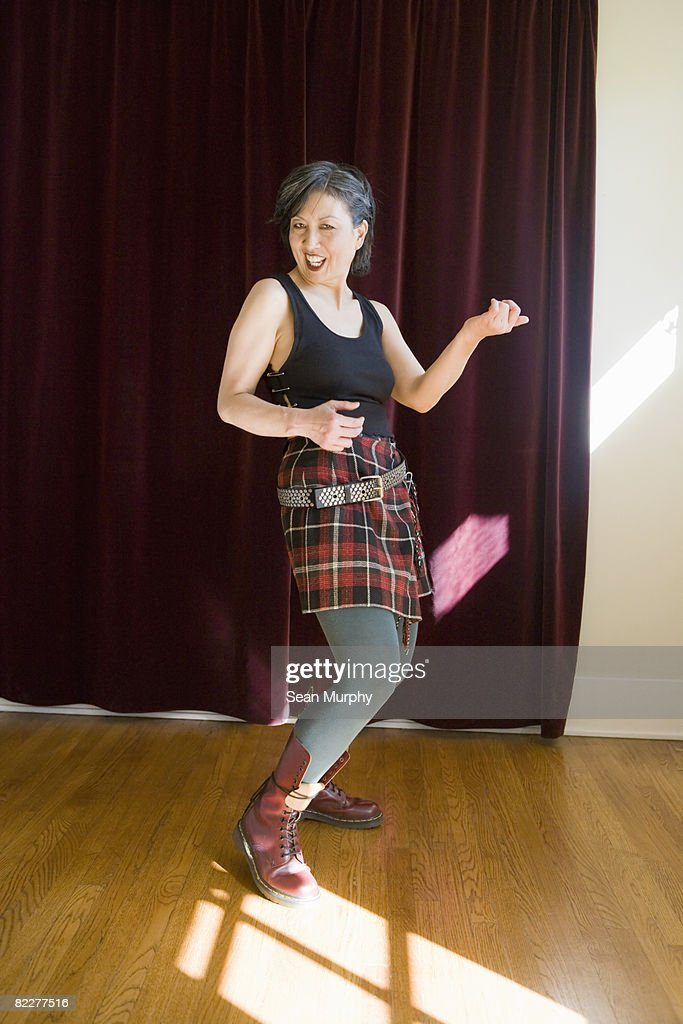 Mature woman in costume playing air guitar