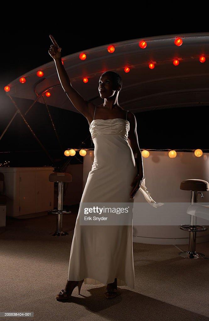 Mature woman in evening dress raising arm on yacht, night : Stock Photo